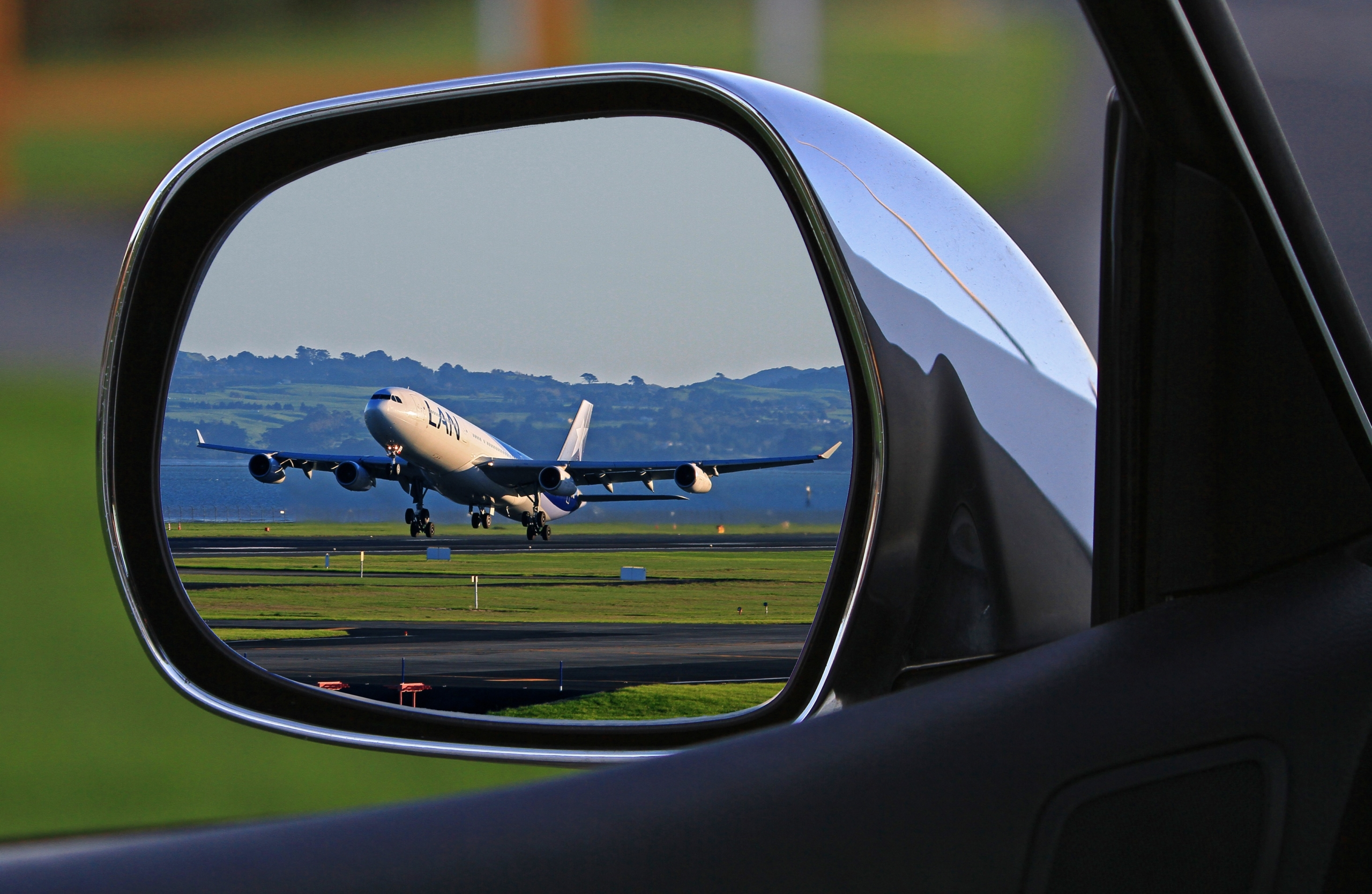 Aeroplane takes off at airport, seen in car mirror