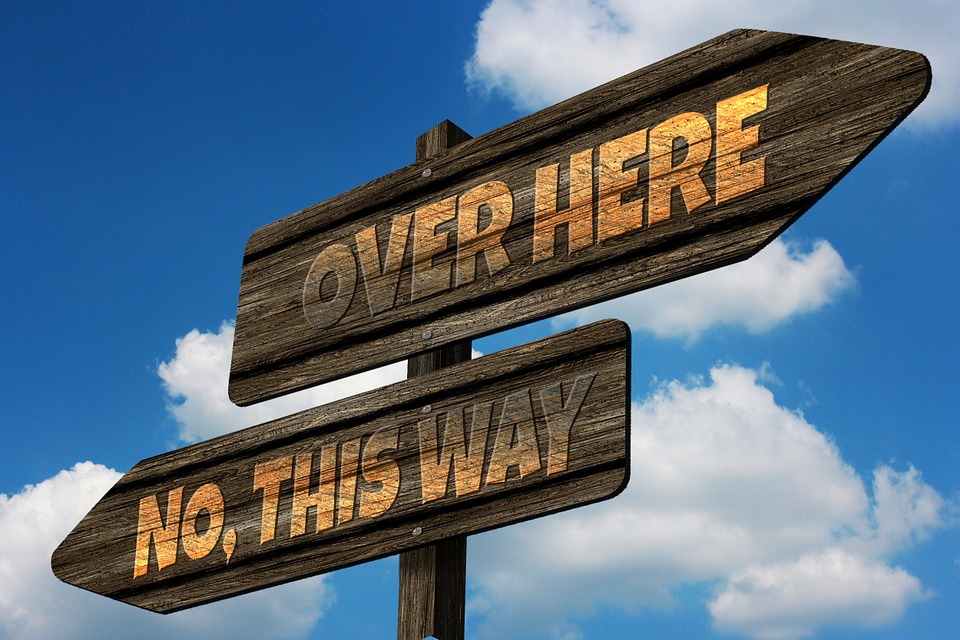 Two signposts, one saying 'over here', the opposite one saying 'no, this way'