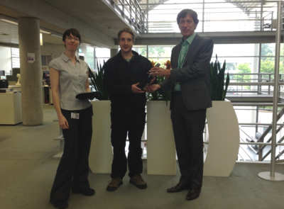 Photo of Georgina Parsons and Simon Bevan presenting Daniel Francis with a bottle of bubbly