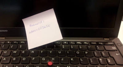 Photo of laptop with a post-it on providing the password
