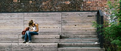 Photo of a girl sitting outside on steps, writing in a notebook