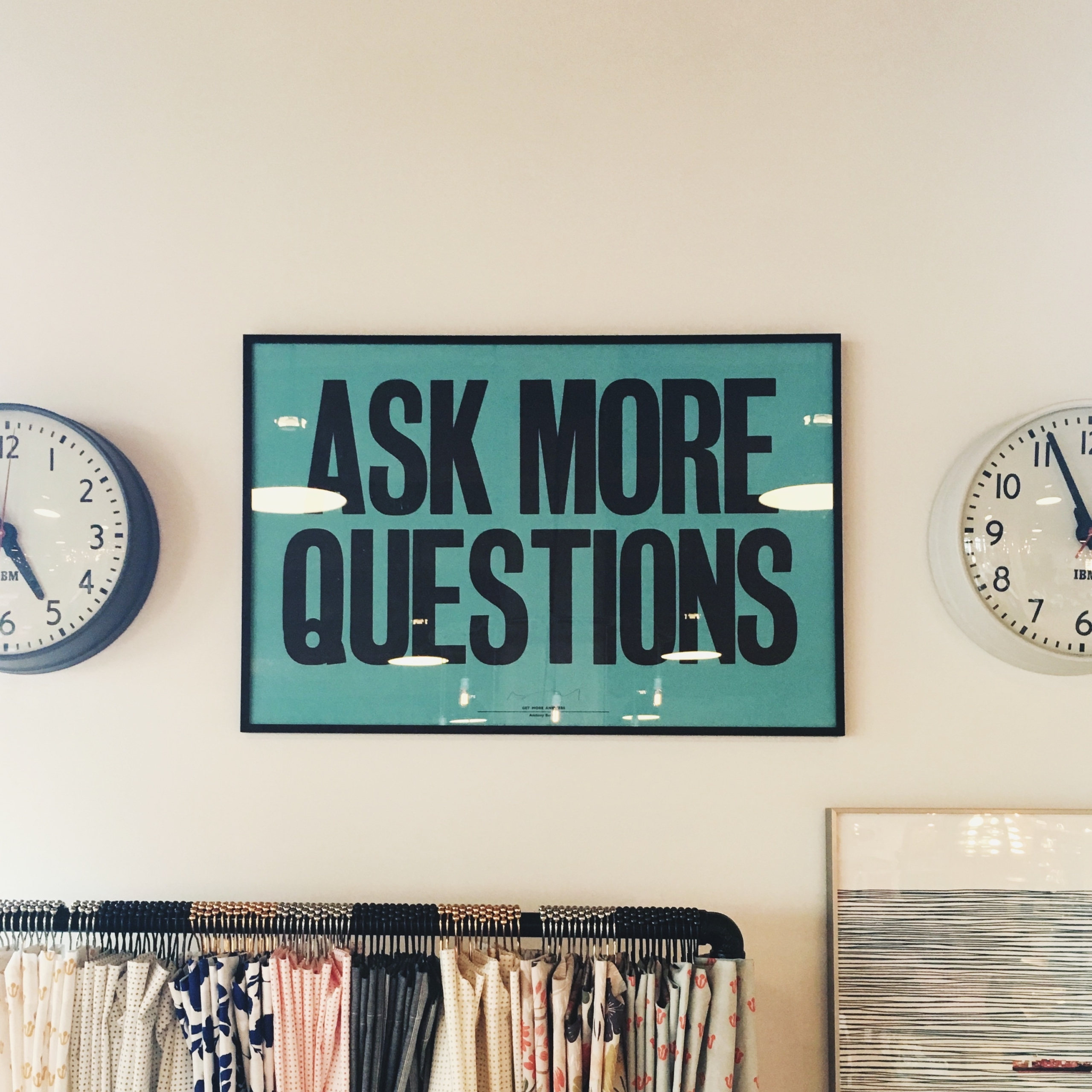 """A framed sign on a wall that reads """"Ask more questions"""""""