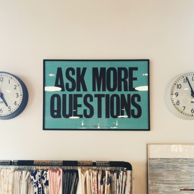"A framed sign on a wall that reads ""Ask more questions"""
