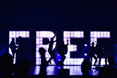 People dancing in front of a lit up sign reading Free