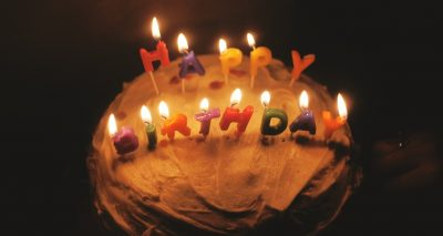 Photo of a cake with candles spelling 'happy birthday'