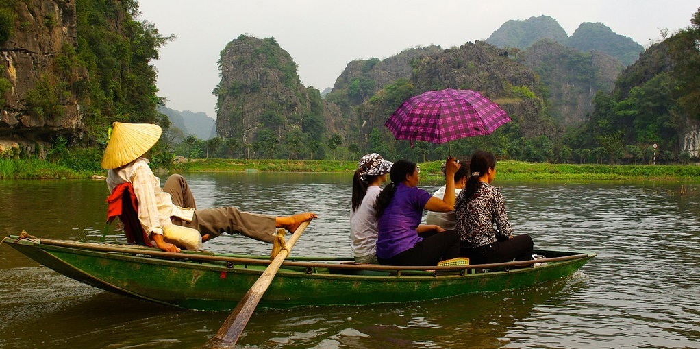 Photo of tourists in a rowing boat on calm waters holding a parasol
