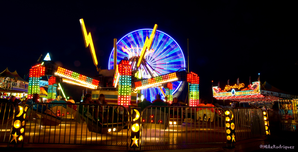 Photo of brightly lit rides at a fairground