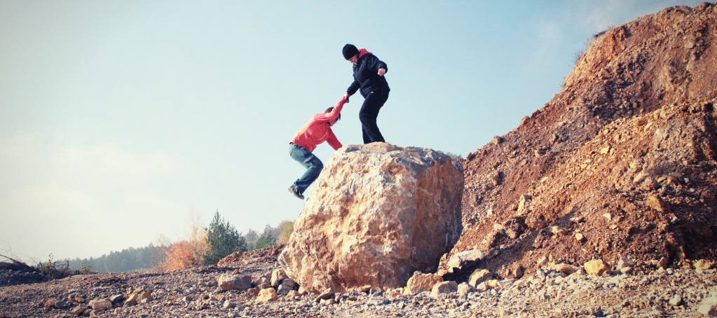 Photo of a person giving another person a helping hand climbing a rock