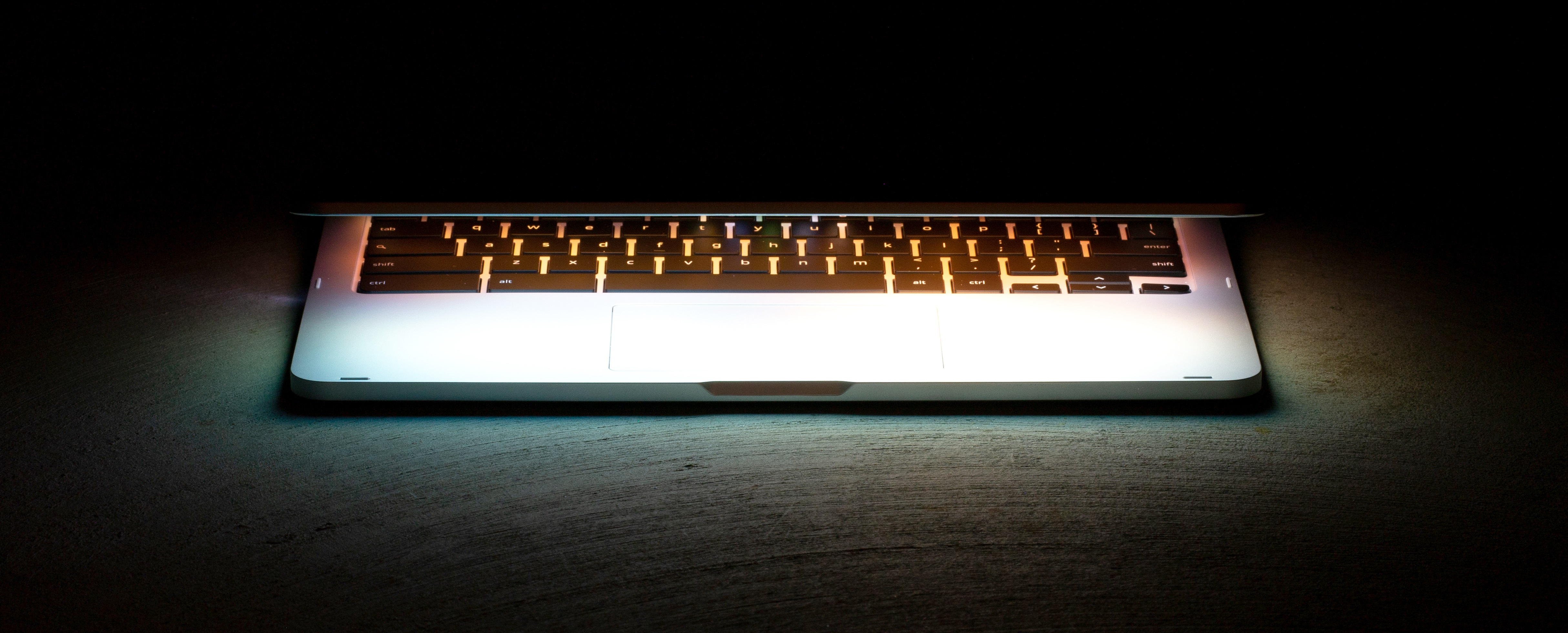 photo of a glowing half-open laptop