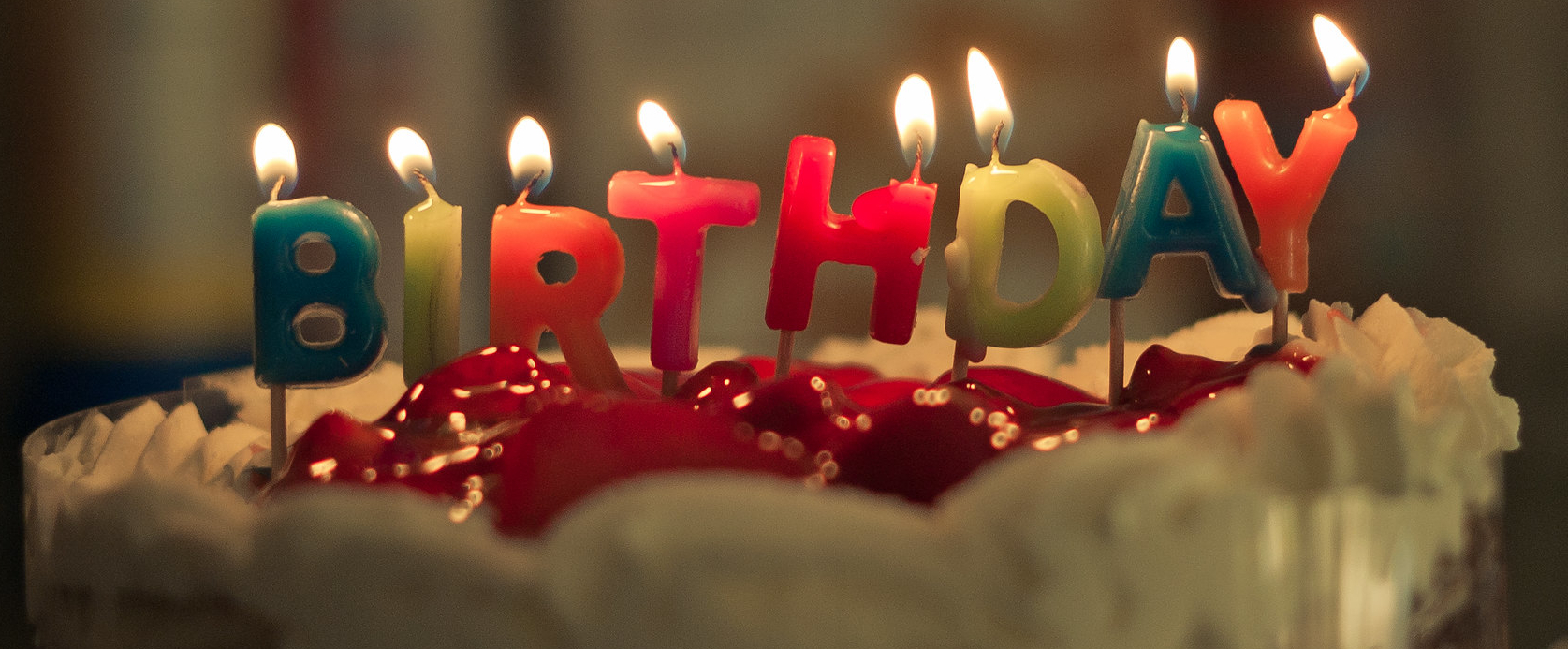 Photo of lit candles on a cake that spell our 'birthday'