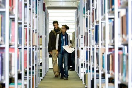 Students walking in the library shelving