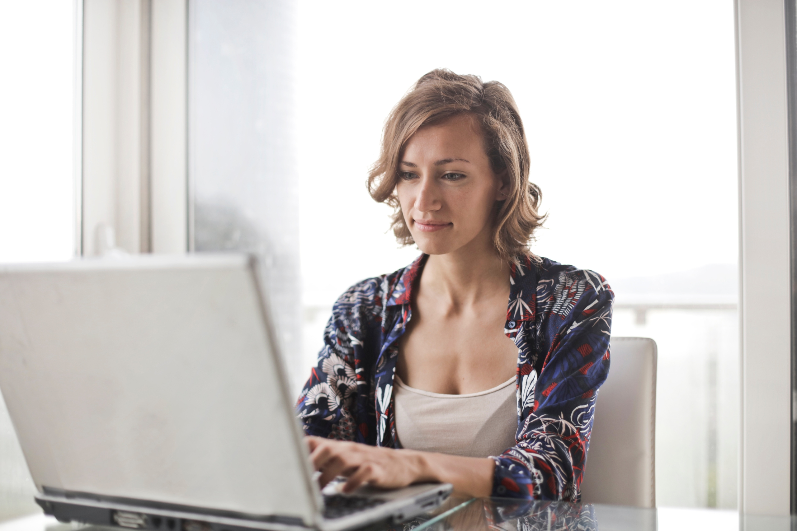 woman-in-blue-floral-top-sitting-while-using-laptop