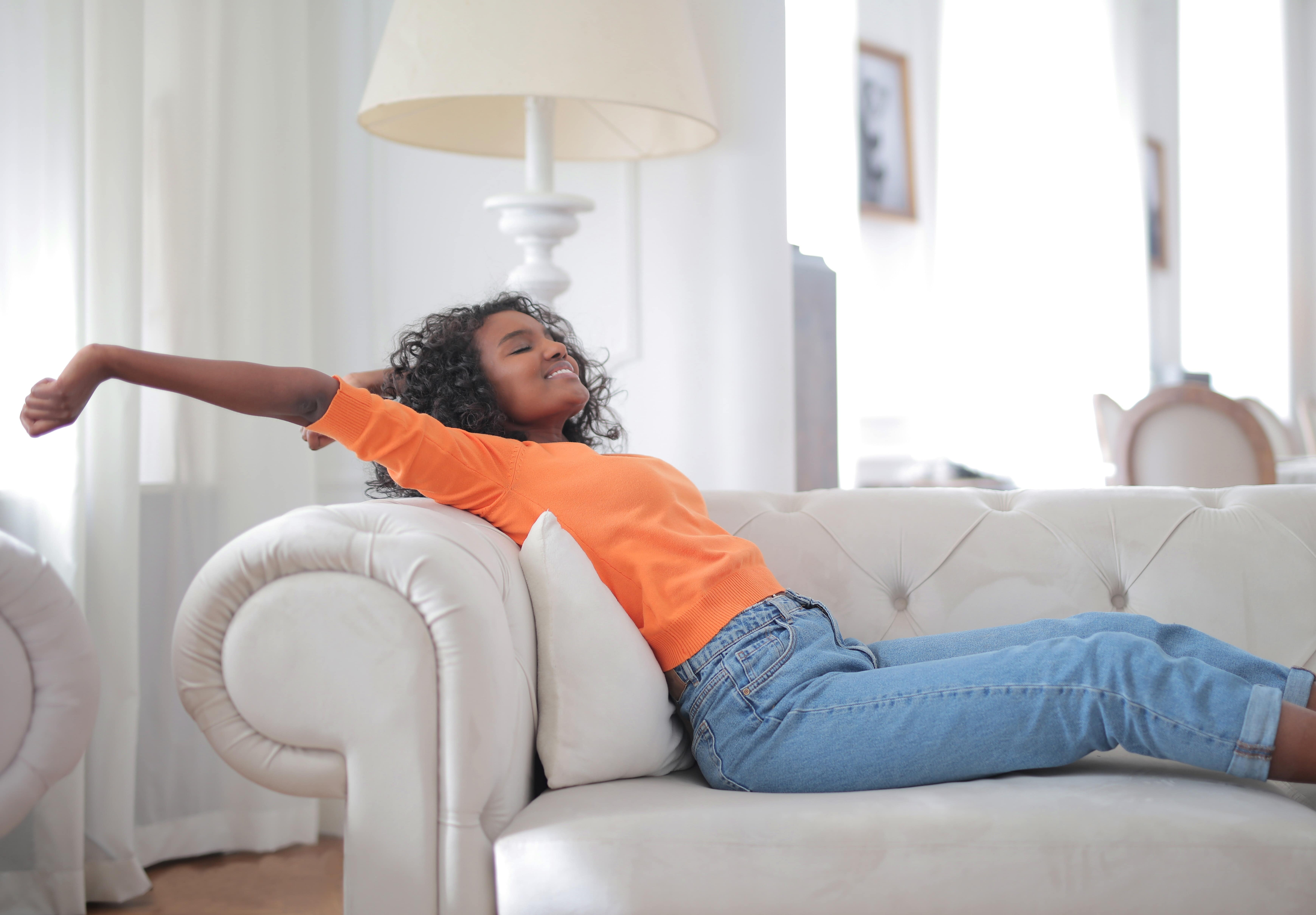 Woman in orange jumper stretching on sofa, she looks relaxed and happy.