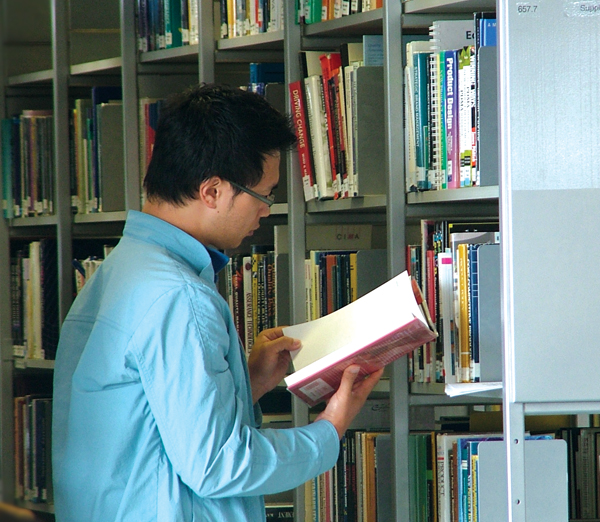 Man reading a book in library shelves