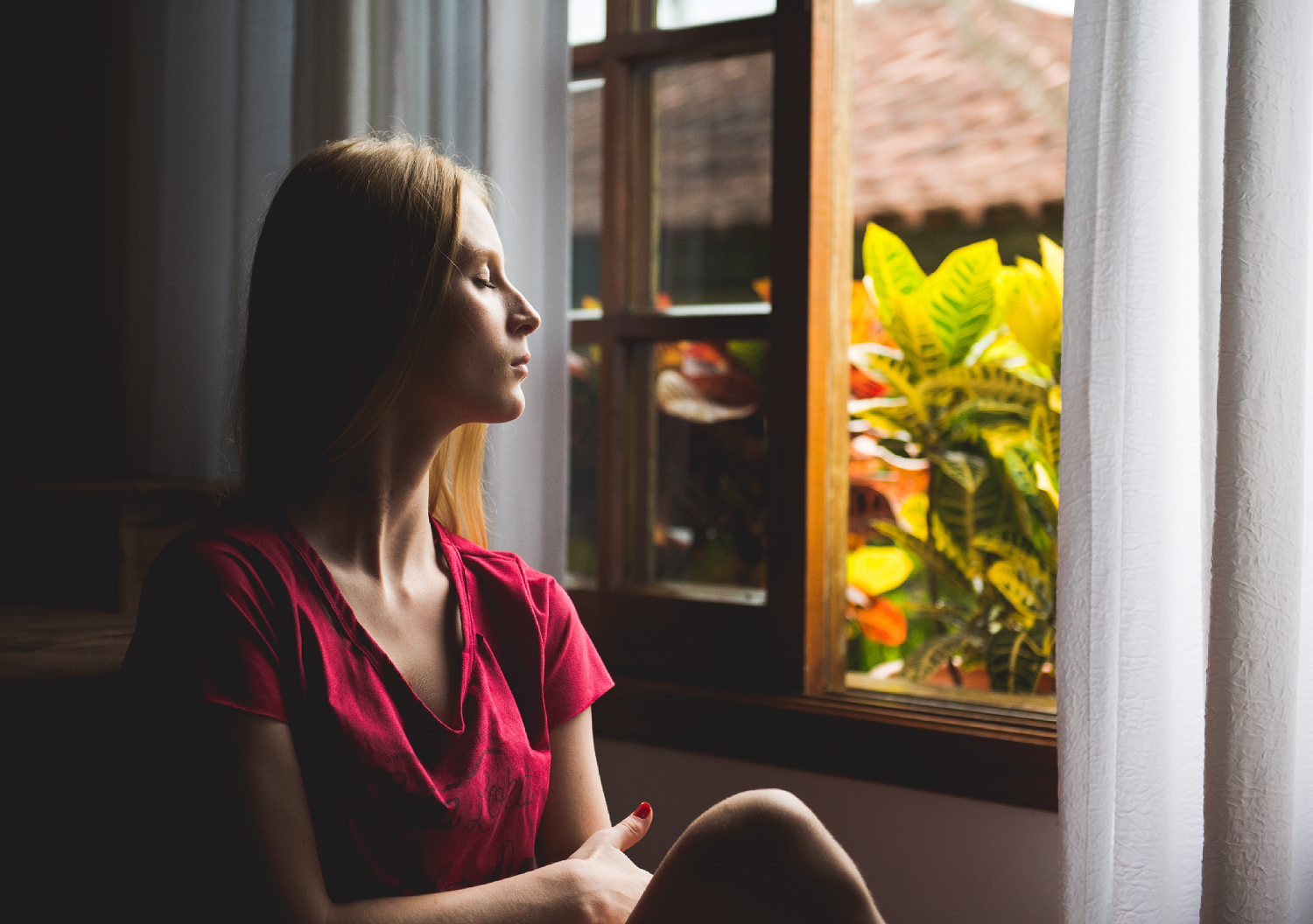 Woman facing towards open window with eyes closed