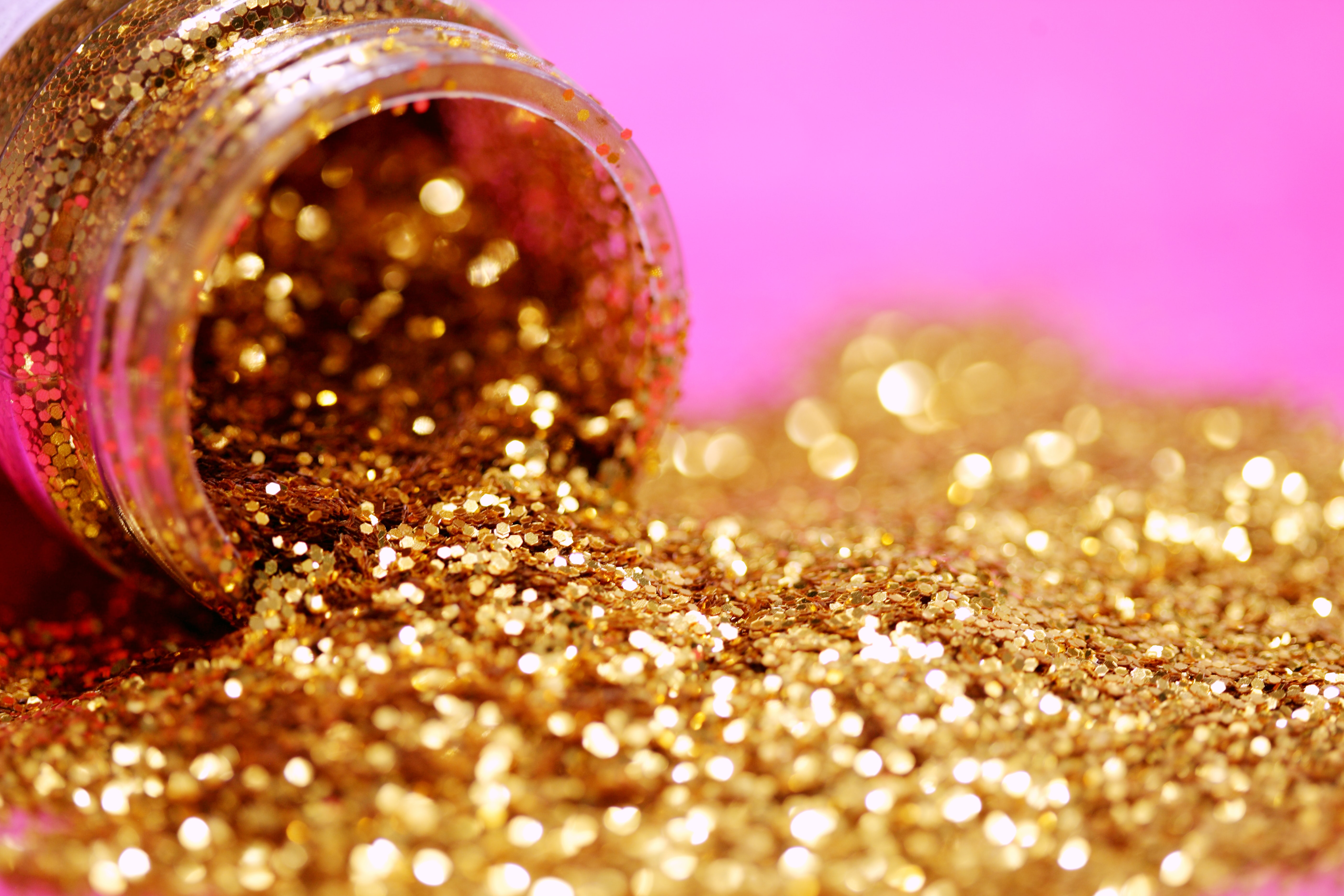 Gold sparkly glittery tumbling out of a jar on a shocking pink background